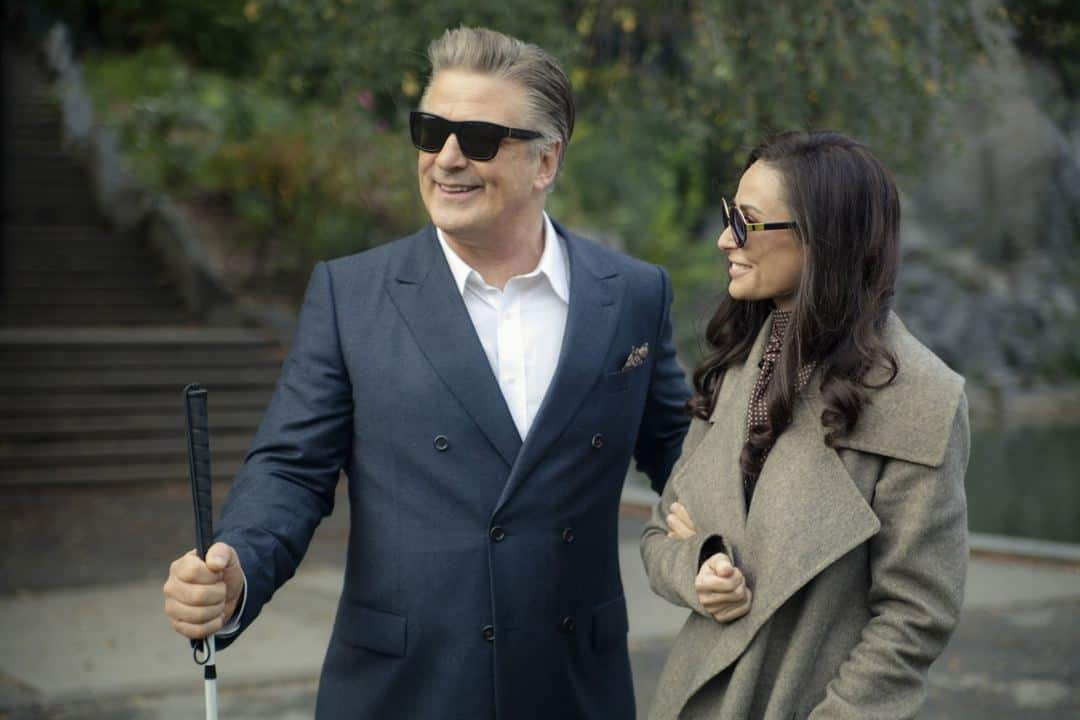 Alec Baldwin (left) wears a dark blue suit jacket, a white shirt and dark glasses. He holds a cane in his right hand and his left hand is tucked under Demi Moore's arm. Demi Moore (right) wears a grey jacket and large fashionable dark glasses. They are both smiling. The background is a public park at daytime with a flight of steps leading up on the left and a tree behind them. They are both standing on a concrete pathway