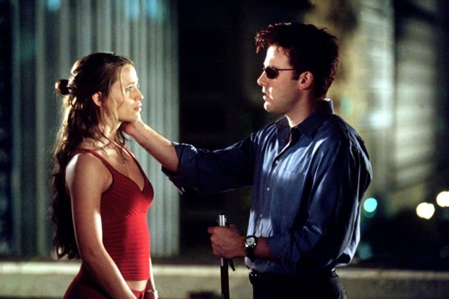 Jennifer Garner (left) and Ben Affleck (right) from 2003. Jennifer Garner wears red clothes, a tight fitting vest top with her midriff showing and red trousers. Her hair is very long and goes down to her waist. Part of her hair is tied at the back of her head. Ben Affleck wears a blue shirt and dark glasses. He is holding a cane with a chrome top in his left hand and has his right hand touching Garner's face. They are both facing each other and presumably lit by moonlight as it is a night scene. The background is a blurred cityscape with a couple of buildings behind them.